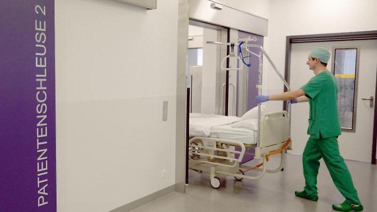 Ein Pfleger schiebt in einem Krankenhaus ein Bett in den Operationstrakt. Foto: Patrick Seeger/dpa/Archivbild