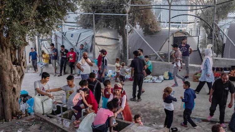Migranten stehen im Flüchtlingslager Moria auf der Insel Lesbos um eine Wasserstelle. Foto: Angelos Tzortzinis/dpa/Archivbild