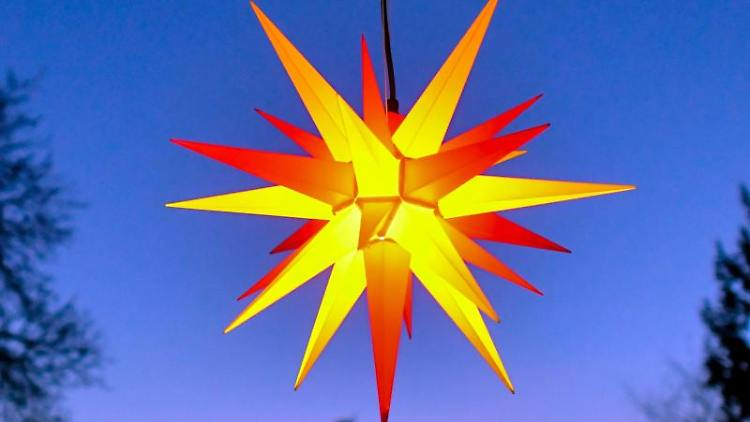 Ein Herrnhuter Stern leuchtet zur blauen Stunde. Foto: Patrick Pleul/zb/dpa/Archivbild