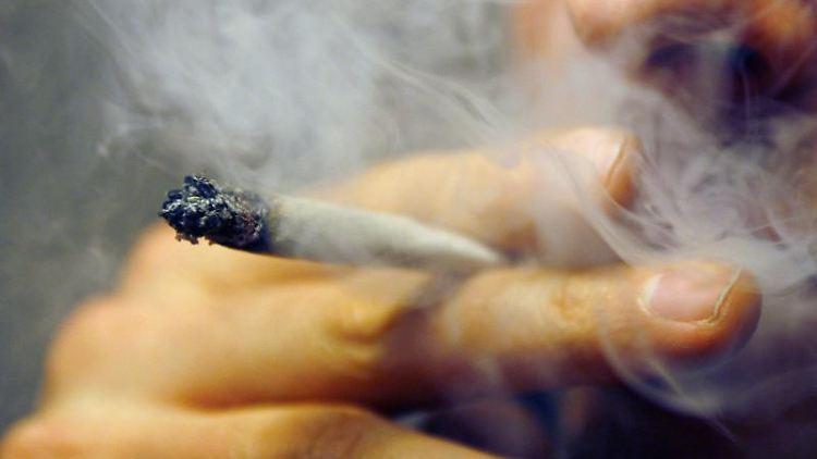Ein Mann raucht einen Joint mit Marihuana. Foto: Daniel Karmann/dpa/Archivbild