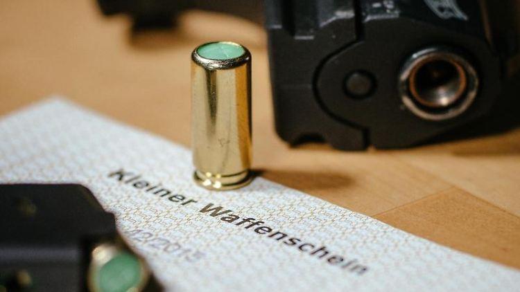 Eine Schreckschusspistole mit einem kleinen Waffenschein. Foto: Oliver Killig/zb/dpa/Symbolbild