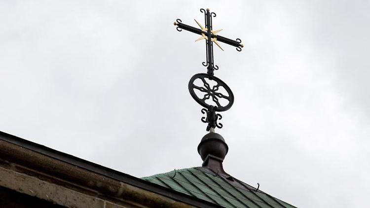 Ein Kreuz auf dem Osnabrücker Dom. Foto: Friso Gentsch/dpa
