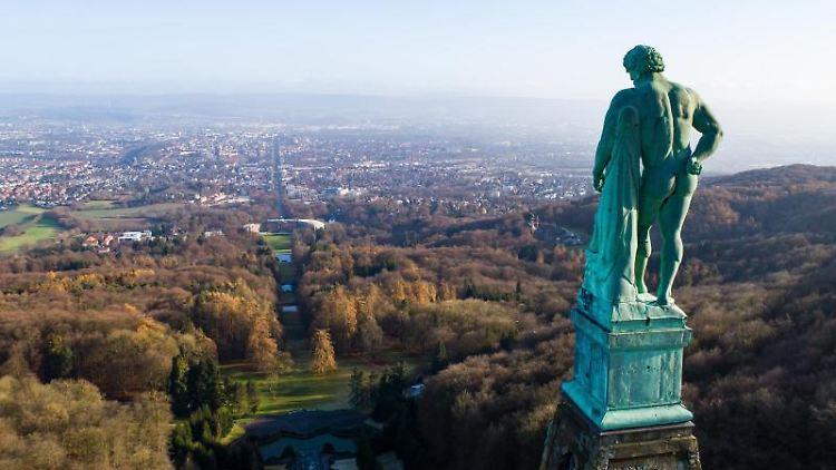Der Herkules, eine Kupferstatue, steht im UNESCO-Weltkulturerbe Bergpark Wilhelmshöhe vor dem Panorama der Stadt Kassel. Foto: Swen Pförtner/dpa/Archivbild
