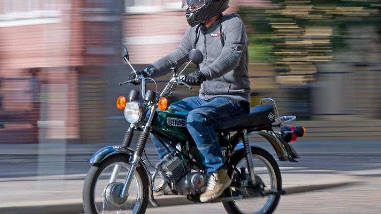 Ein Mann fährt auf einem Simson S51 Moped über die Straße. Foto: Hendrik Schmidt/zb/dpa