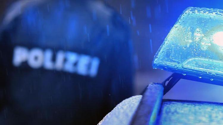 Ein Polizist steht im Regen vor einem Streifenwagen dessen Blaulicht aktiviert ist. Foto: Karl-Josef Hildenbrand/dpa/Symbolbild