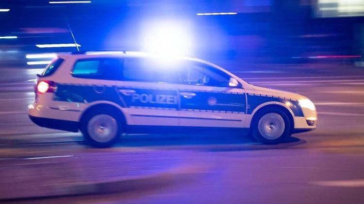 Ein Polizeiauto fährt unter Einsatz von Blaulicht und Sirene eine Straße entlang. Foto: Lino Mirgeler/dpa/Archivbild