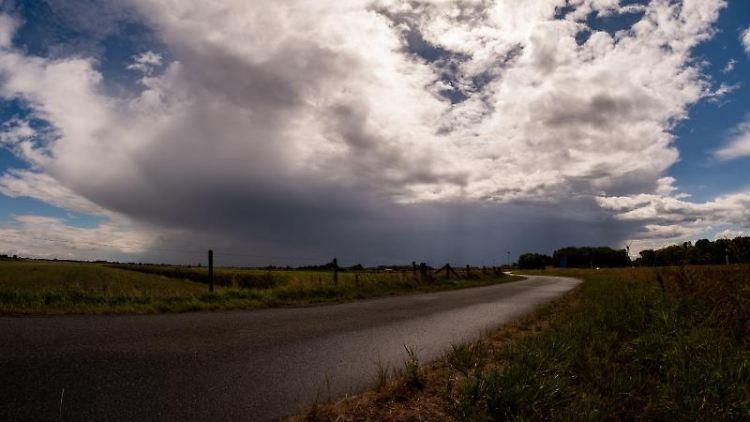 Wolken ziehen sich über einem Feld vor der Sonne zusammen. Foto: Mohssen Assanimoghaddam/dpa/Archiv