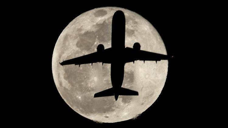 Ein Flugzeug vor dem Mond. Foto: Ringo Chiu/ZUMA Wire/dpa