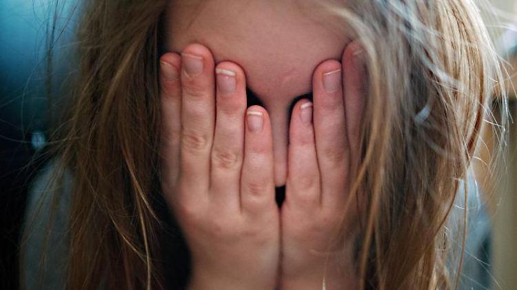 Mädchen hält sich Hände vor das Gesicht. Foto: Nicolas Armer/dpa