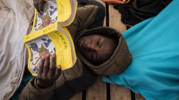 Gauro, 15, aus Mali, liest ein Buch über Europa. Foto: Santi Palacios/AP/dpa