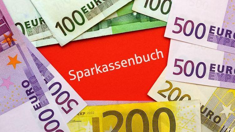 Ein Sparkassenbuch unter Euro-Geldscheinen. Foto: Patrick Pleul/dpa-Zentralbild/dpa