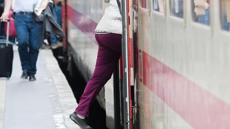 Eine Frau steigt in einen IC. Foto: Julian Stratenschulte/dpa/archiv