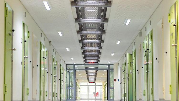 Verschlossene Zellen in einem Gang einer JVA. Foto: Christophe Gateau/dpa/Archivbild