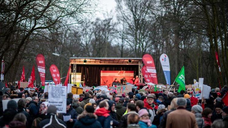 Teilnehmer einer Gegendemonstration stehen vor einer Bühne des Deutschen Gewerkschaftsbundes (DGB). Foto: Fabian Strauch/dpa