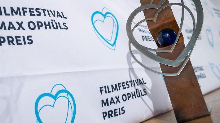 Ein Trophäe des Filmfestivals Max Ophüls Preis steht neben einem Banner mit dem Logo des Festivals. Foto: Oliver Dietze/dpa/Archivbild