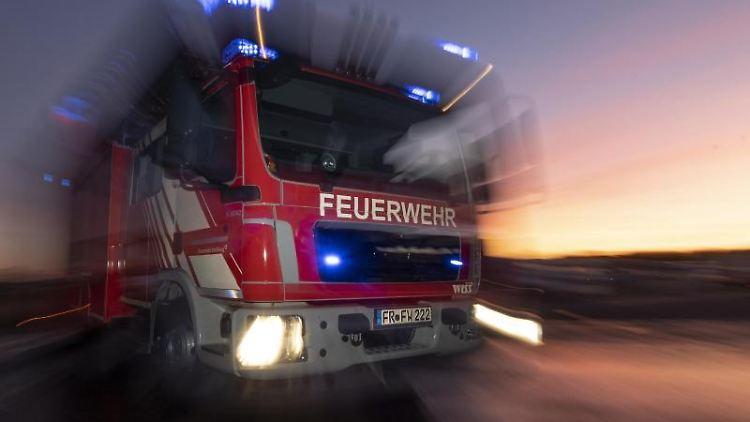Ein Feuerwehrfahrzeug steht mit eingeschaltetem Blaulicht auf einer Straße. Foto: Patrick Seeger/dpa/Archivbild