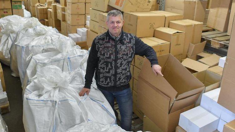 Andreas Steinert, Unternehmer, steht in einem Lager voller Kartons und weißen Säcken voller Kleider. Foto: Patrick Pleul/zb/dpa/Archivbild