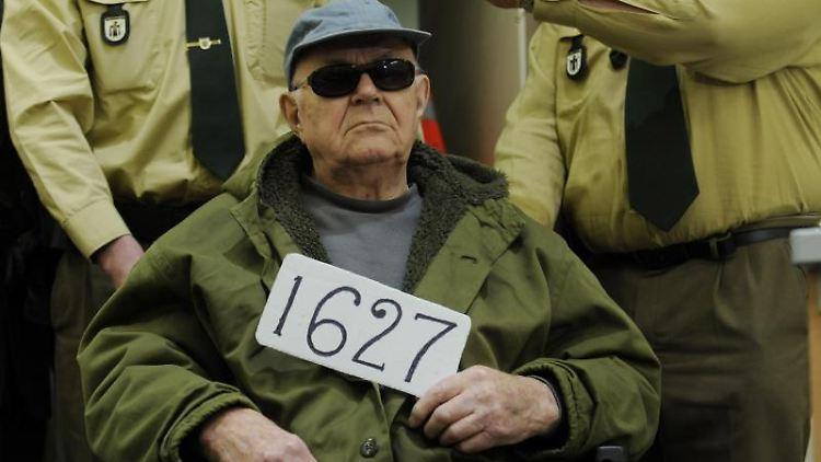 John Demjanjuk sitzt vor Polizeibeamten im Rollstuhl. Foto: Lukas Barth/dpa/Archivbild
