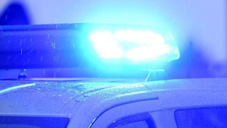 Ein Polizeiwagen mit eingeschaltetem Blaulicht steht am Rande einer Demonstration in Kiel. Foto: Carsten Rehder/dpa