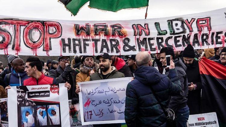 Menschen demonstrieren am Rande der Libyen-Konferenz gegen den libyschen General Haftar. Foto: Paul Zinken/dpa