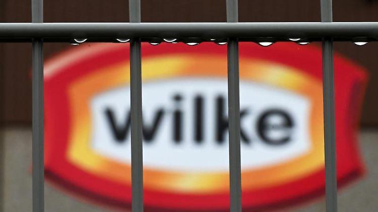 Wassertropfen hängen am Zaun vor dem Logo des nordhessischen Wurstherstellers Wilke. Foto: Uwe Zucchi/dpa/Archivbild