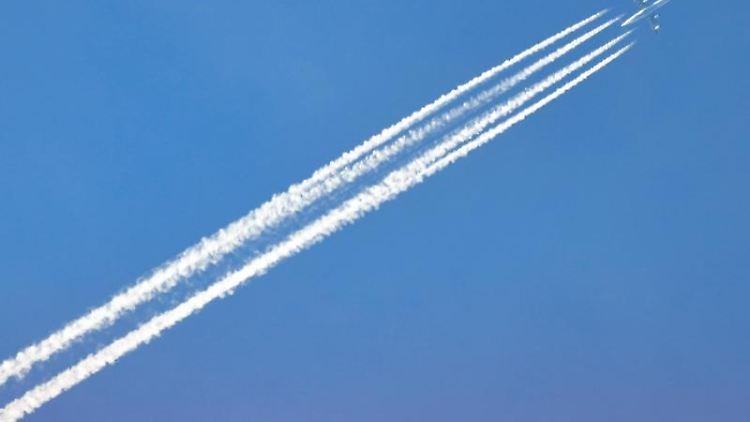 Ein Flugzeug zieht Kondensstreifen hinter sich her. Foto: Soeren Stache/dpa-Zentralbild/dpa/Archivbild