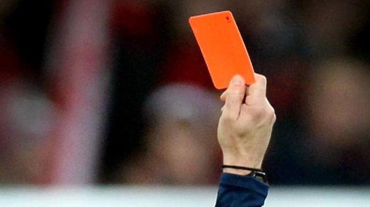 Ein Schiedsrichter zeigt eine rote Karte. Foto: Patrick Seeger/dpa/Symbolbild