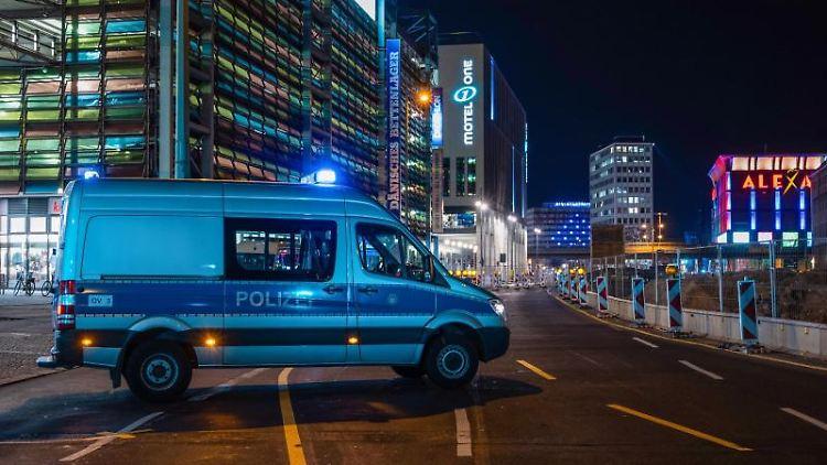 Ein Polizeiauto sperrt die Grunerstraße ab. Foto: Christophe Gateau/dpa