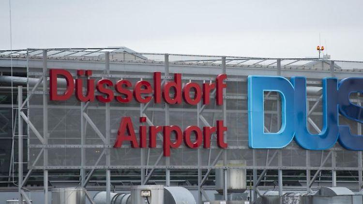 Das Logo des Flughafens Düsseldorf an der Fassade des Terminals. Foto: Christophe Gateau/dpa/Archivbild