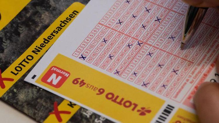 Eine Frau füllt einen Lottoschein aus. Foto: Swen Pförtner/dpa/Archivbild