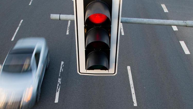Ein Auto fährt an einer roten Ampel vorbei. Foto: Julian Stratenschulte/dpa/Archivbild