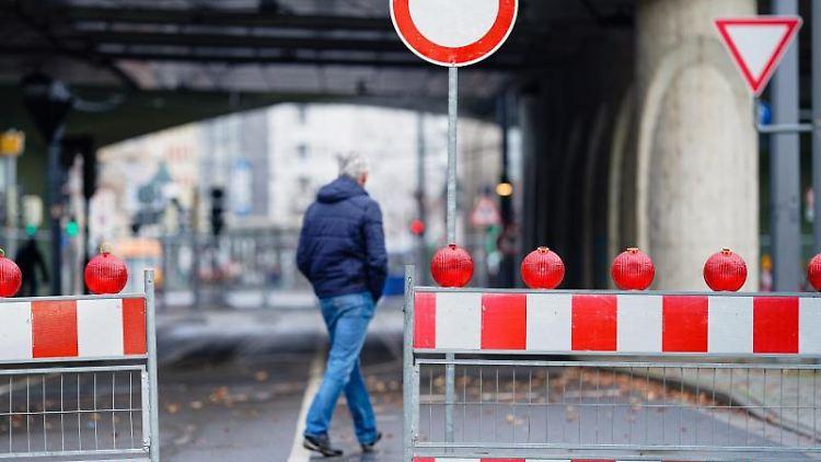 Ein Mann geht an der Hochstraße Süd an einer Straßensperre vorbei. Foto: Uwe Anspach/dpa