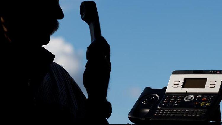 Ein Mann hält einen Telefonhörer in der Hand. Foto: Julian Stratenschulte/Archiv