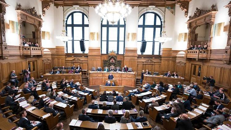 Abgeordnete verfolgen die Sitzung der Hamburgischen Bürgerschaft im Rathaus. Foto: Daniel Reinhardt/dpa