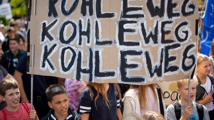 Klimademonstranten stehen mit ihrem Transparent mit der Aufschrift