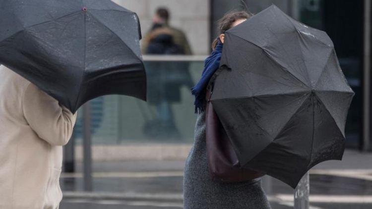 Eine heftige Sturmböe erfasst die Schirme von zwei Passantinnen. Foto: Boris Roessler/dpa/Archivbild