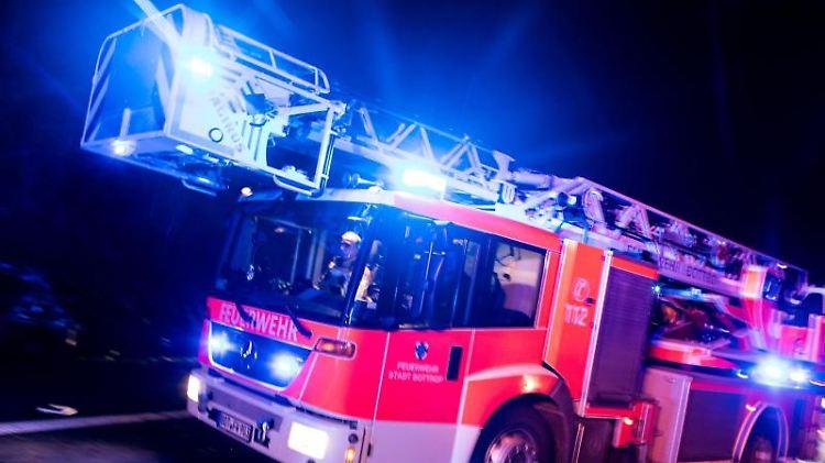 Ein Drehleiterwagen der Feuerwehr fährt mit Blaulicht über eine Straße. Foto: Marcel Kusch/dpa/Symbolbild