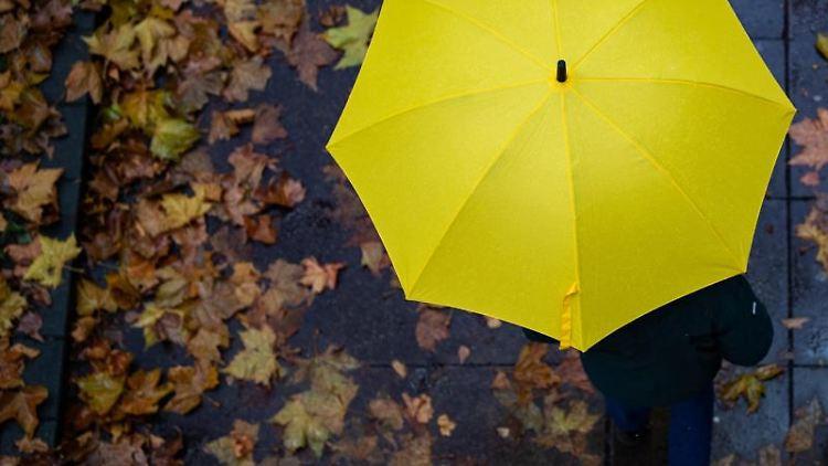 Eine Person läuft mit einem Regenschirm auf einem Gehweg. Foto: Tom Weller/dpa