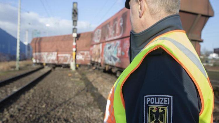 Ein Bundespolizist steht vor einem entgleisten Güterzug. Foto: Jörg Sarbach/dpa