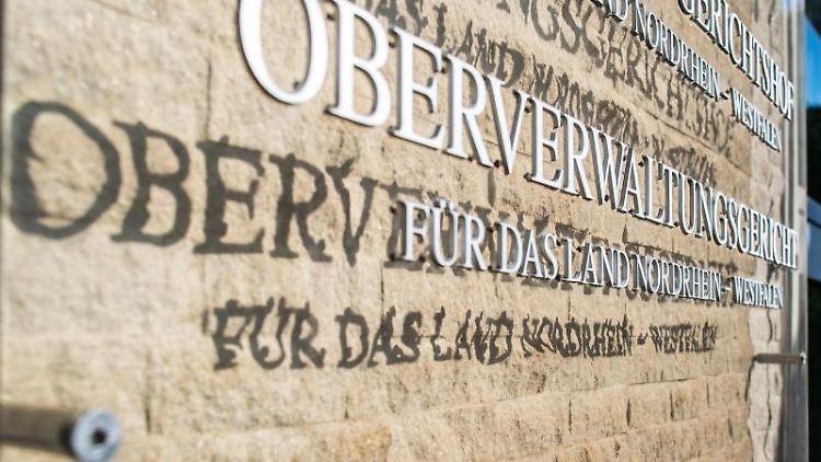 An der Aussenfassade am OVG hängt eine Hinweistafel mit dem Landeswappen von NRW. Foto: Guido Kirchner/dpa