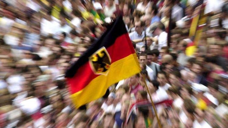 Man kann die deutsche Fahnen inmitten von unzähligen Fans sehen. Foto: picture-alliance / dpa/dpaweb /Archivbild
