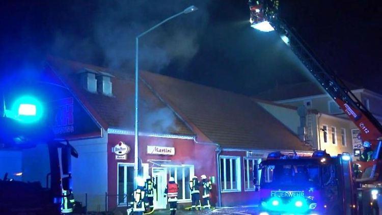 Feuerwehrleute löschen aus dem Korb einer Drehleiter heraus den Brand in einem Restaurant. Foto: --/TNN/dpa