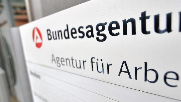 Besucher der Agentur für Arbeit gehen durch eine Tür. Foto: Hendrik Schmidt/dpa-Zentralbild/dpa