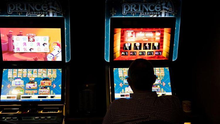 Ein Mann sitzt an einem Spielautomaten in einer Spielhalle. Foto: Julian Stratenschulte/dpa/Archivbild