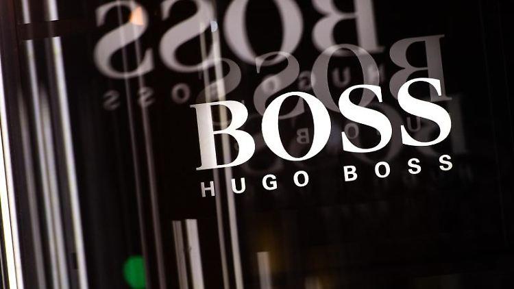 Das Logo von Hugo Boss spiegelt sich in mehreren Glasscheiben. Foto: Sebastian Gollnow/dpa/Archivbild