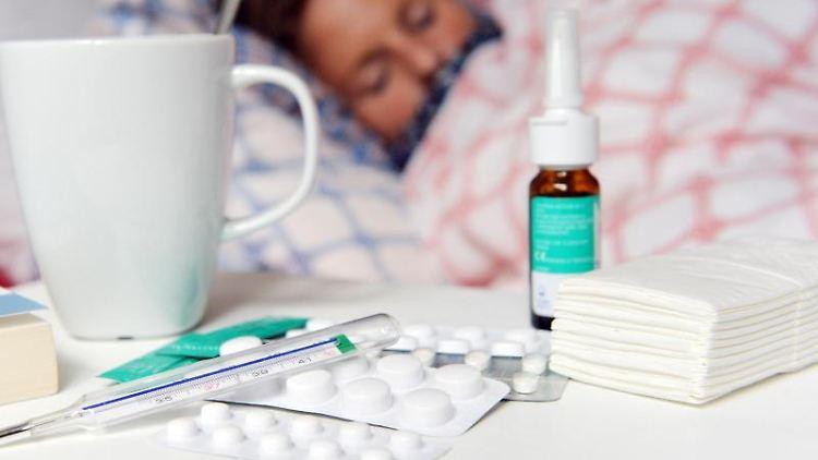 Medikamente und ein Fieberthermometer liegen auf einem Nachttisch. Foto: Maurizio Gambarini/dpa/Archivbild
