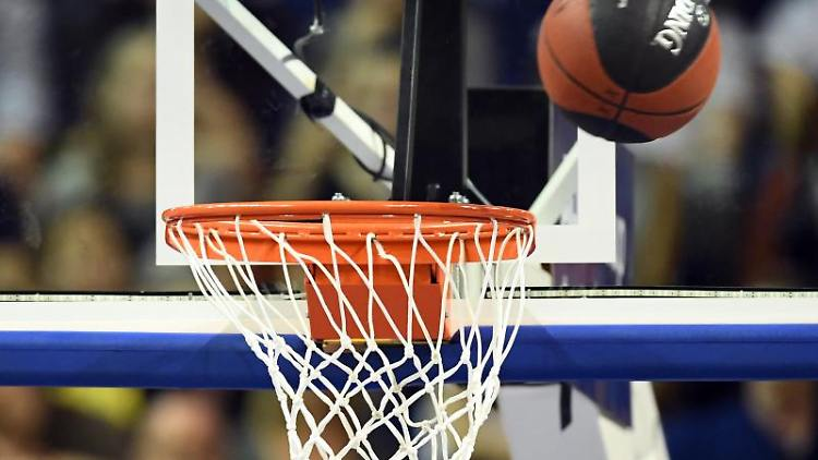 Ein Basketball fliegt auf den Korb zu. Foto: Soeren Stache/dpa/Archivbild