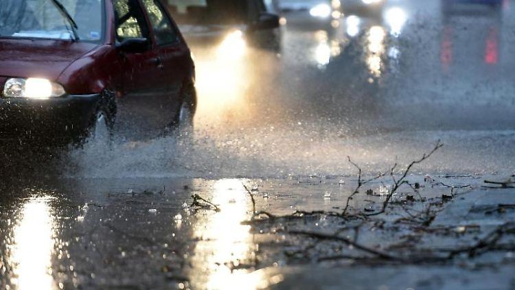 Autos fahren langsam durch eine tiefe Pfütze die sich durch Starkregen auf einer Straße gebildet hat. Foto: Caroline Seidel/dpa/Archivbild