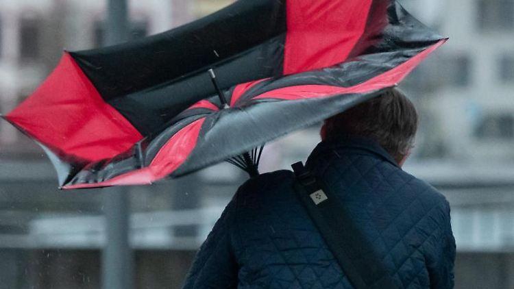 Der Regenschirm eines Spaziergängers ist wegen einer Windböe umgeklappt. Foto: Bernd Thissen/dpa