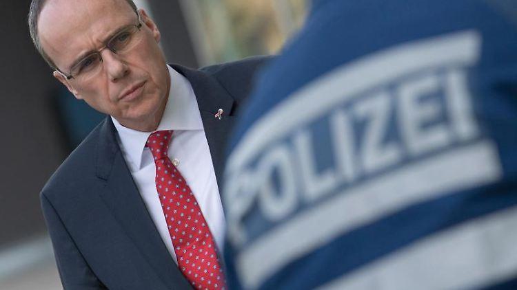 Peter Beuth (CDU) steht hinter einem Polizisten. Foto: Boris Roessler/dpa/Archivbild